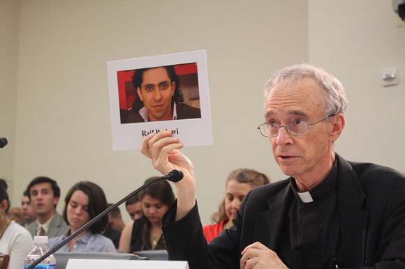 USCIRF Chair Thomas J. Reese, S.J., holds up a photo of Raif Badawi at a July 2016 Tom Lantos Human Rights Commission hearing on Blasphemy Laws
