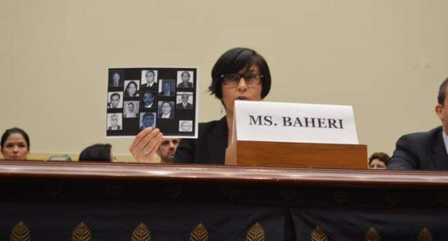 Ms. Cler Baheri, a member of the Baha'i community, holds up a photo of imprisoned Baha'is in Iran.