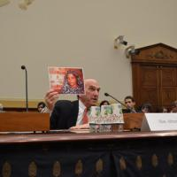 USCIRF Commissioner Elliott Abrams holds up a photo of a prisoner of conscience.